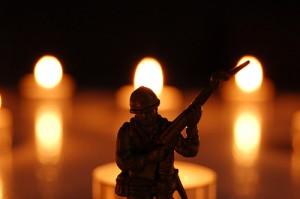 A toy soldier in front of tea lights