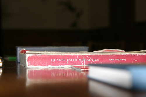 A well-worn copy of Quaker Faith & Practice lying on a table