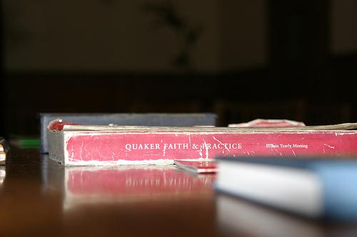 A well-worn copy of Quaker Faith & Practice lying on a table