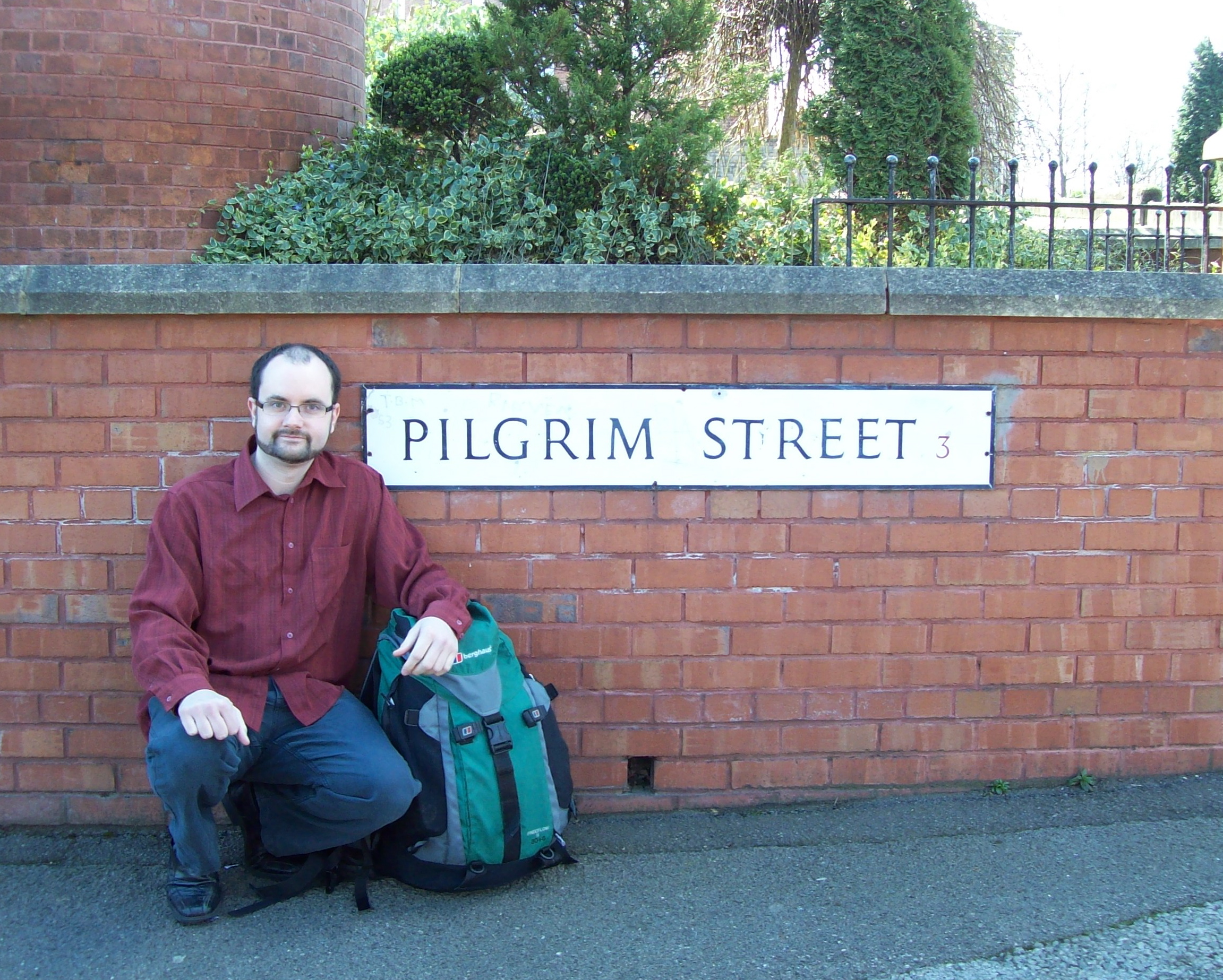 Symon Hill crouched by a sign for Pilgrim Street