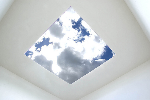 Clouds edged with silver light seen through a skyspace