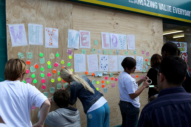 People adding messages to a board about why they love Peckham