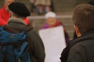 Quaker worship with two people with their backs to the viewer and out of focus a woman holding a sign about Quakers.