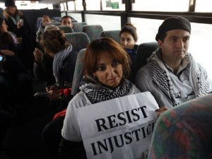 Palestinians on a bus for Israeli settlers with a sign 'resist injustice'