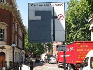 A road sign rendered meaningless by blacked out parts because of the Olympics