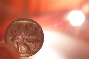 A 2 Rand coin in the foreground with sunlight in the background