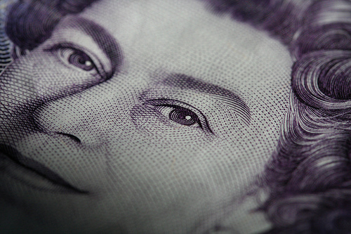 Part of the British queen's face from a bank note, showing her eyes.