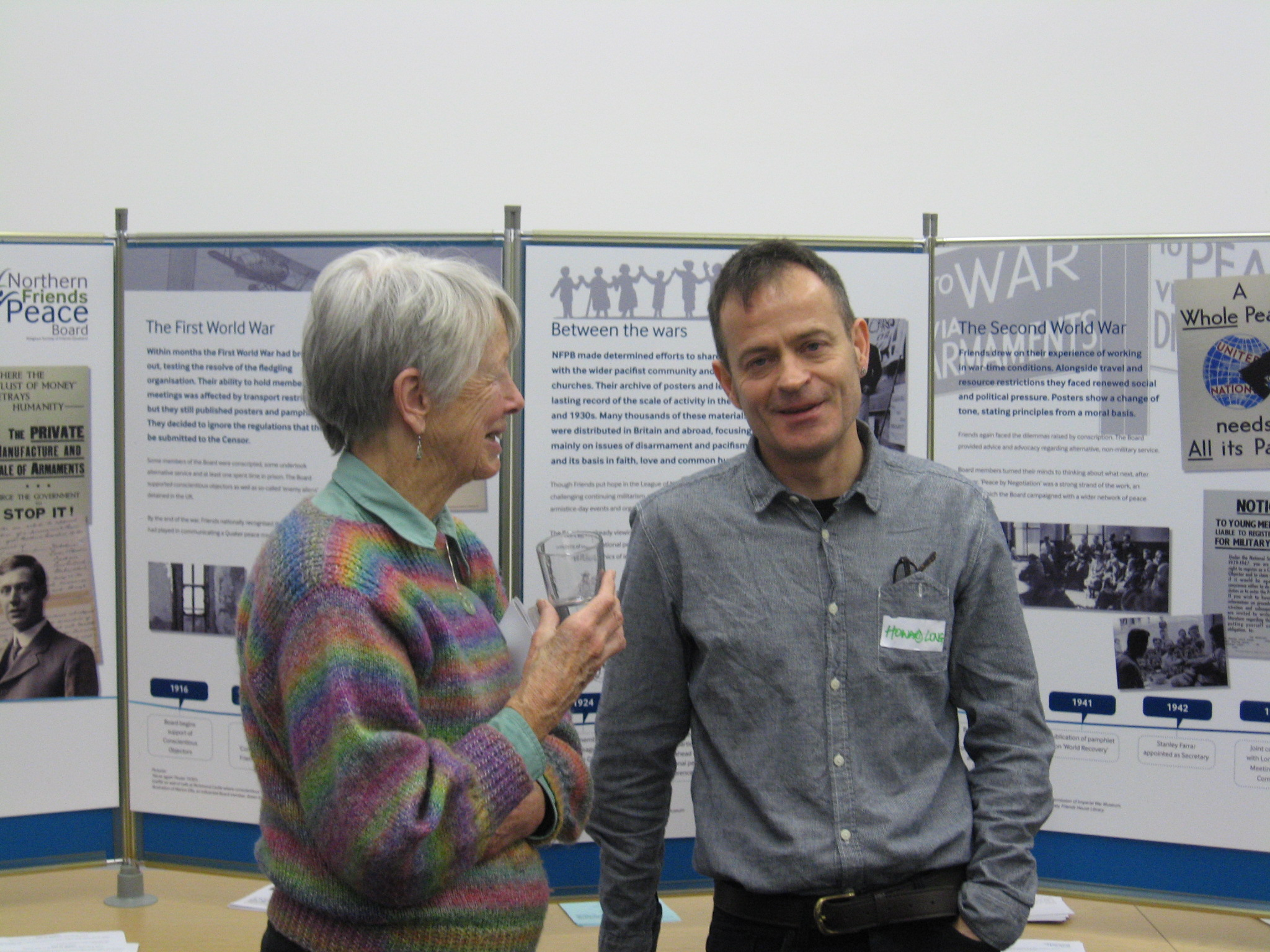 Two people chatting in front of display boards to celebrate 100 years of NFPB.