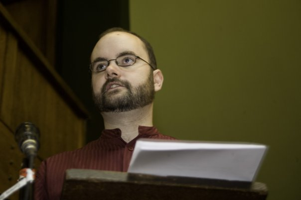 Symon Hill stands at a lectern