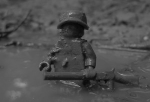 A lego soldier up to his waist in mud