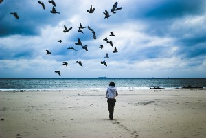A woman on a beach with footbprints behind her and a flock of birds in the sky