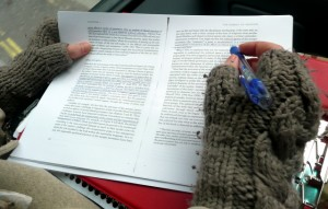 A book being marked by a reader on the bus, wearing woolly gloves