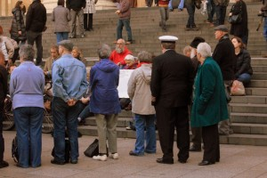 People standing facing into the circle, with passersby around them.