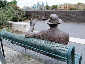 View of Alfred Salter statue from rear, with daughter's statue in front of him and view of City of London in background.
