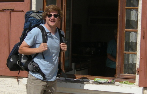 Drew standing with his backpack on next to an open window