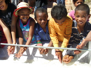 Children test out the new water supply at their school. Photo: Money for Madagascar